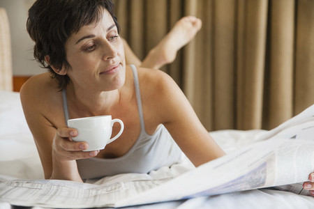 Woman relaxing on bed with coffee and reading newspaper