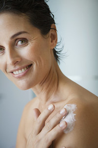 Portrait happy woman applying moisturizer to shoulder
