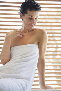 Woman wrapped in a towel in bathroom