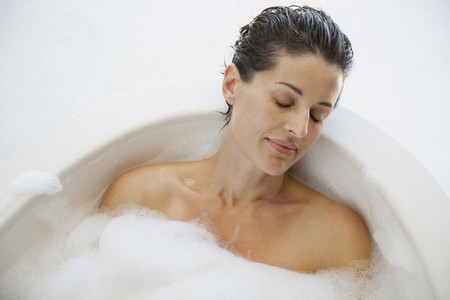 Serene woman enjoying bubble bath