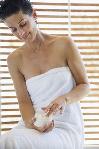 Woman in towel applying moisturizer in bathroom