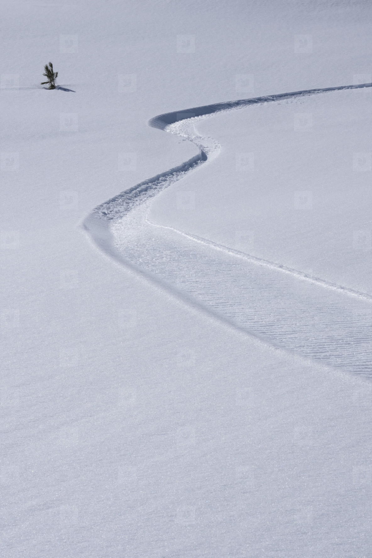 Winding path on sunny snowy slope