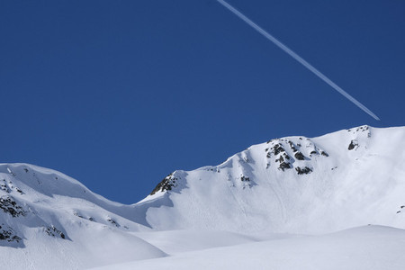 Airplane contrail in sunny blue sky above snowy mountain
