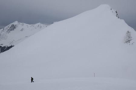 Man snowshoeing below snowy mountain