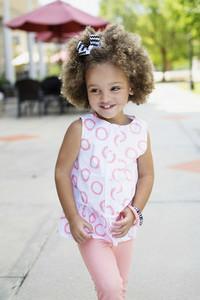 Portrait cute girl in pink on sidewalk