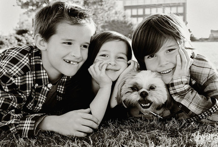 Portrait cute brothers and sister with dog laying in grass