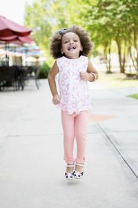 Portrait cute girl in pink jumping on sidewalk