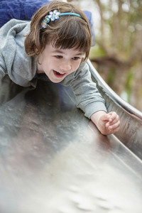 Portrait happy girl going down slide head first