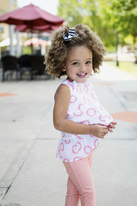 Portrait smiling girl in pink and white on sidewalk