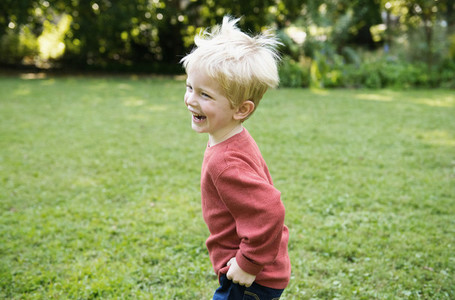 Happy boy laughing and running in grass