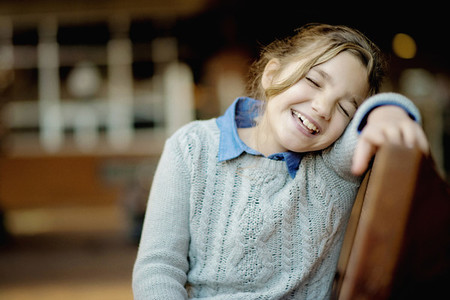 Girl laughing with eyes closed on bench