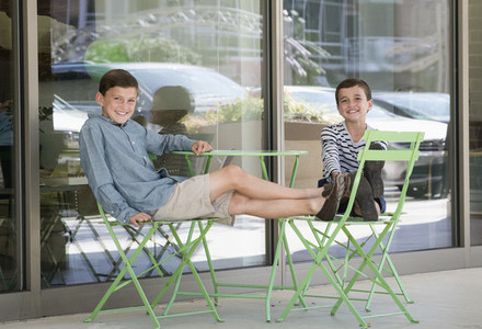 Portrait carefree brothers relaxing with feet up at sidewalk cafe