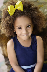 Portrait cute girl with yellow bow in hair