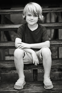 Portrait boy in shorts and t shirt sitting on wooden steps