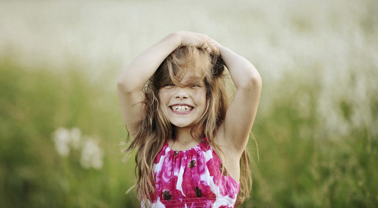 Portrait happy carefree teenage girl with hands in hair in field