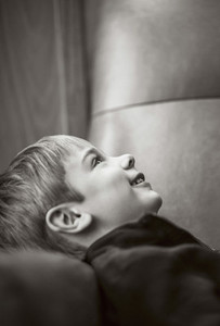 Happy boy laying in armchair looking up