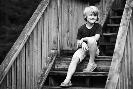 Smiling boy sitting on wooden steps