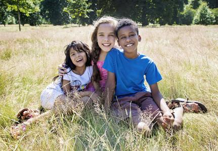 Portrait happy kids sitting in sunny field
