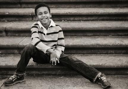 Portrait confident boy sitting on urban steps