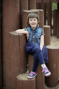 Portrait cute  smiling girl on wooden posts