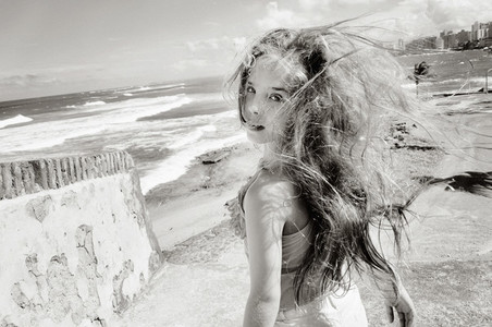 Portrait carefree teenage girl on windy ocean beach