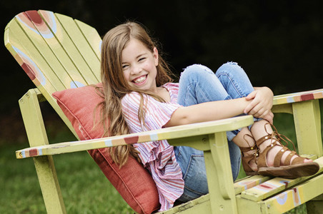 Portrait happy girl sitting in adirondack chair