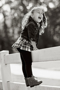 Portrait exuberant girl laughing on fence