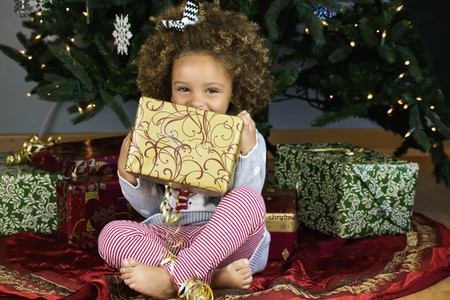 Portrait cute girl holding Christmas present under tree