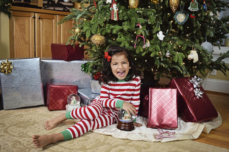 Portrait playful girl in pajamas with snow globe and presents under Christmas tree