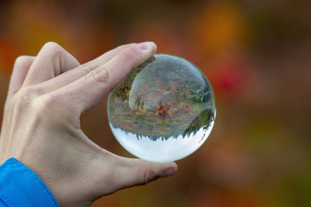 Personal perspective hand holding crystal orb reflecting autumn landscape