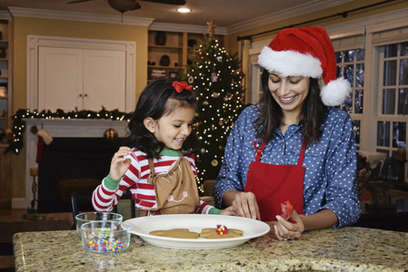 Mother and daughter baking gingerbread cookies for Christmas