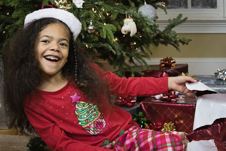 Portrait excited girl in pajamas opening Christmas presents