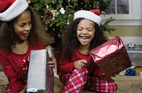 Laughing sisters in pajamas opening Christmas presents