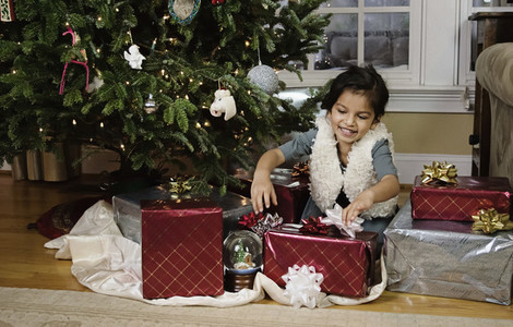 Happy girl opening presents under Christmas tree