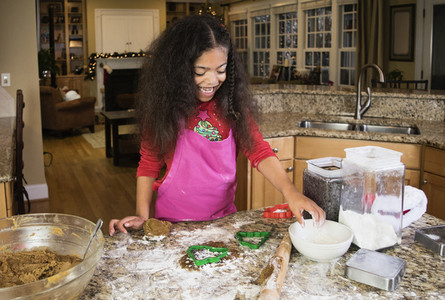 Happy girl baking Christmas cookies at kitchen counter