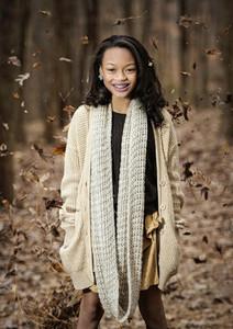 Autumn leaves falling around smiling girl