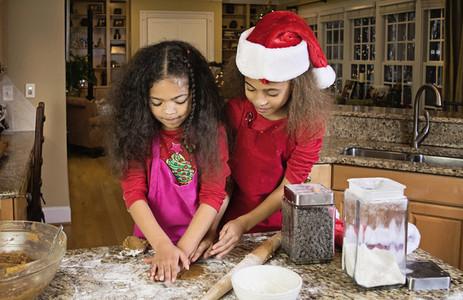 Sisters baking Christmas cookies at kitchen counter