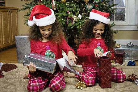Happy sisters in pajamas opening Christmas gifts by tree
