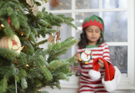 Girl in pajamas with Santa hat by Christmas tree