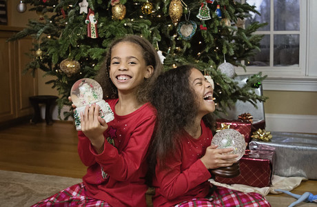 Portrait happy sisters with snow globes in front of Christmas tree