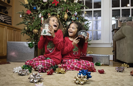 Happy sisters in pajamas with snow globes by Christmas tree