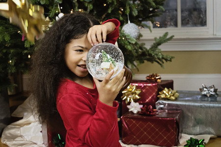 Cute girl with snow globe by Christmas tree