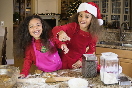 Portrait happy sisters baking Christmas cookies at kitchen counter