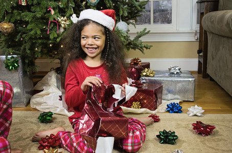 Happy girl in pajamas opening Christmas gift by Christmas tree