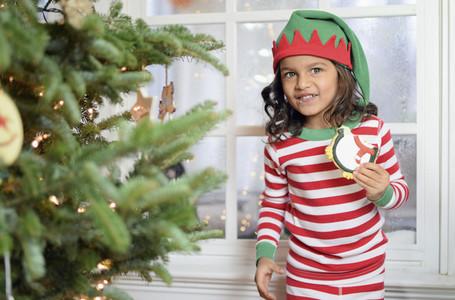 Portrait cute girl in pajamas eating cookie by Christmas tree