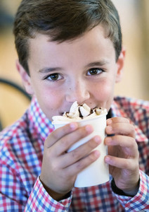Portrait cute boy drinking hot cocoa with whipped cream