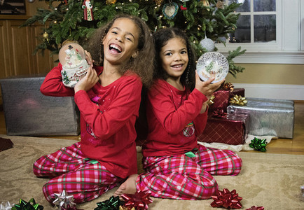 Portrait happy sisters in pajamas with snow globes in front of Christmas tree