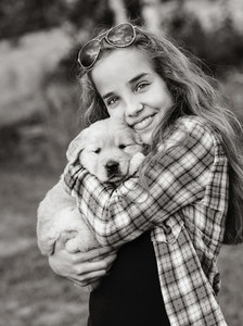 Portrait teenage girl holding Golden Retriever puppy