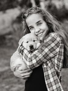 Portrait teenage girl holding Golden Retriever puppy