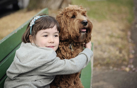 Cute girl hugging dog on park bench